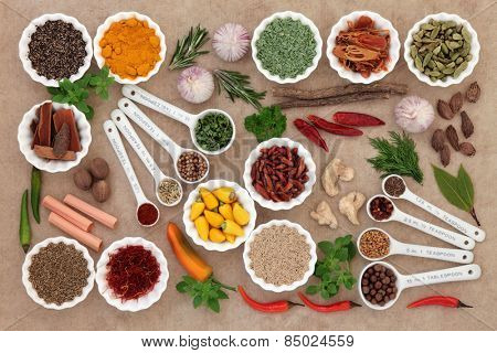 Herb and spice collection in measuring spoons and crinkle bowls.