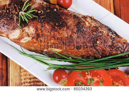 main course on wood: whole fried sunfish on plate with lemons and peppers