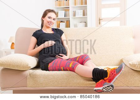 Young pregnant woman resting after doing finess at home