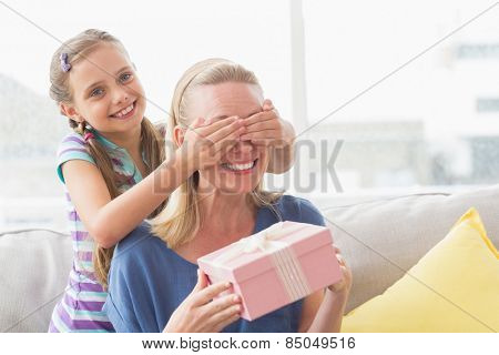 Happy mother holding gift with daughter covering her eyes at home in living room