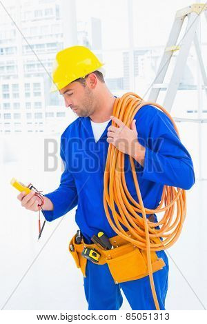 Male electrician with wire roll looking at reading multimeter in bright office