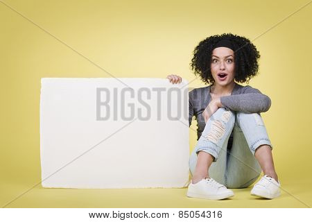 Excited girl being astonished by amazing news holding a blank white paper sign board with copy space.
