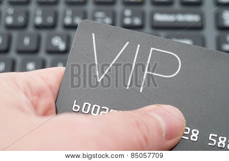 Hand holding VIP card against keyboard background