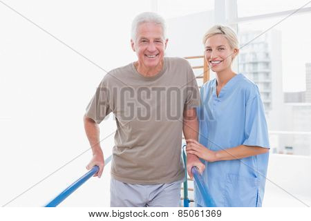 Senior man an therapist smiling at camera in fitness studio