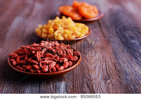 Dried fruits in small plates on rustic wooden table background