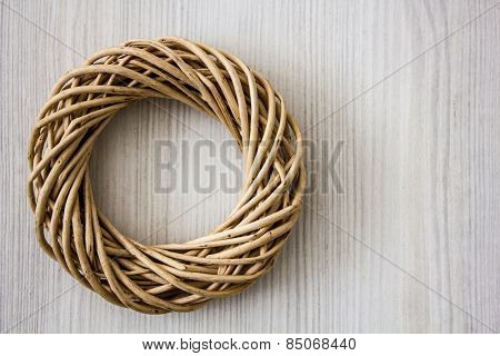 Tied twigs and branches in shape of circle on white wooden background