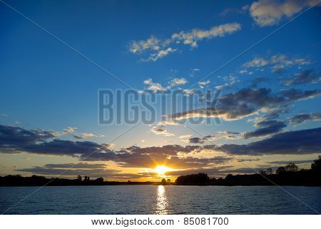 Sunset Over The Lake On A Background Of Blue Sky