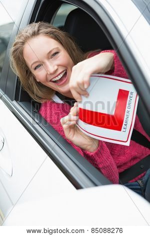 Learner driver smiling and holding l plate in her car