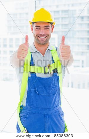 Portrait of construction worker wearing safety harness while gesturing thumbs up in bright office