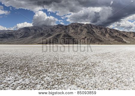 Mojave desert dry lake salt flat with dark storm clouds.