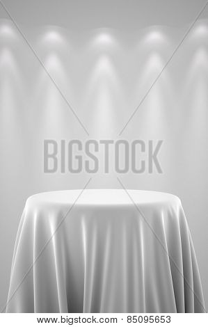Round presentation pedestal covered with a white silk cloth in front of a wall illuminated by spot lights
