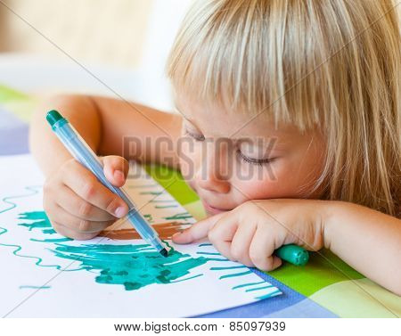 Cute little girl sitting at a table drawing