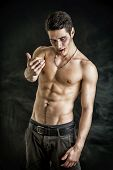 Portrait of a Young Vampire Man Shirtless Showing his Torso Chest and Abs Gesturing to Camera Looking at the Camera on Dark Background. poster
