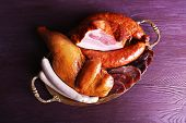 Assortment of deli meats on metal tray on color wooden background poster