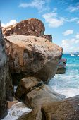 Close up Huge Granite Rocks at the Baths in Beautiful Virgin Gorda Island with Boats Sailing Afar Under Light Blue and White Sky. poster