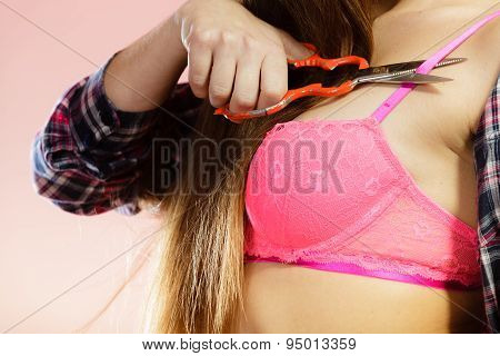 Bosom concept. Closeup female chest in pink lace bra. Woman taking off her lingerie holding scissors in hand cutting bra strap. Dressing up. poster