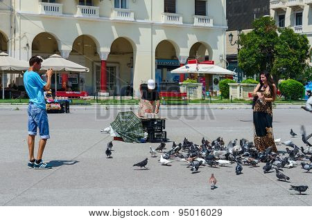 Young Man And Woman Are Feeding Pigeons On Square Of Aristotle In Thessaloniki, Greece