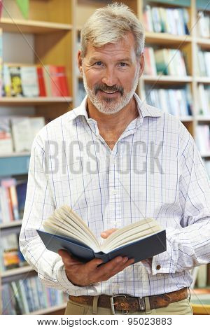 Portrait Of Male Customer Reading Book In Bookstore