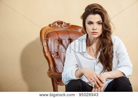 Attractive young girl is situated on chair