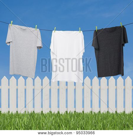 Close Up Of Three T-shirts On The Rope (grey, White And Dark Grey). Outside Background With Sky And