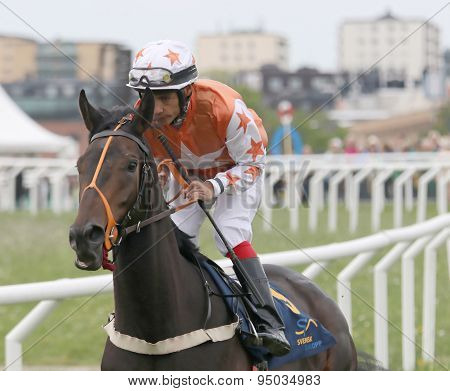 Man In Orange Clothes Riding A Race Horse