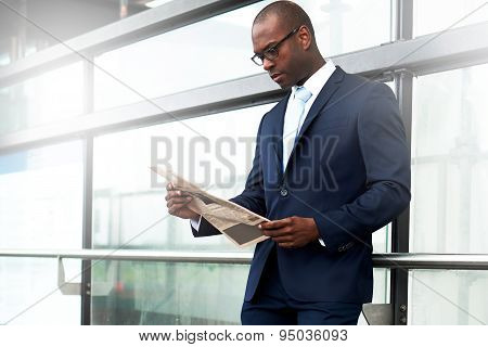 Businessman Reading Newspaper At The Walkway Side