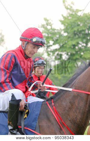 Two Jockeys Sitting On Their Race Horses