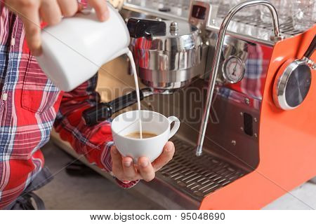 Close-up of man pouring milk in cup