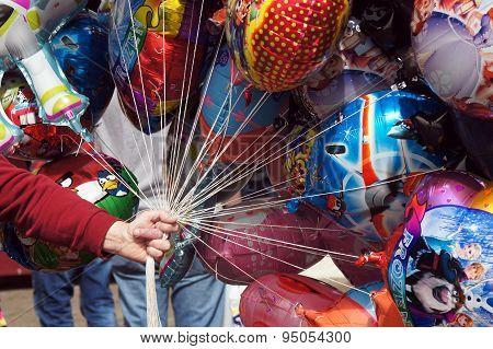 Balloon seller holding colorful balloons