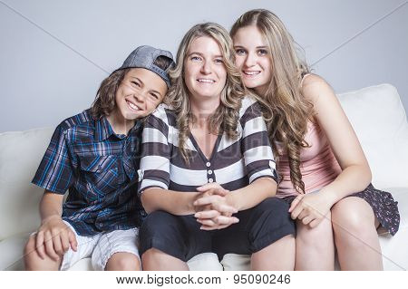 affectionate mother son daughter sitting on sofa
