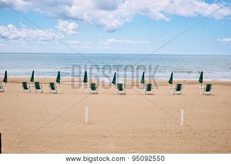 A beach with umbrellas and sun beds on coast