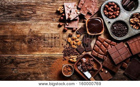 Assortment of different chocolate types on wooden background, top view with copy space.