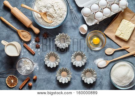 The process of making cake dough. Baking ingredients for homemade pastry on dark background. Bake sweet cake dessert concept. Top view, flat lay