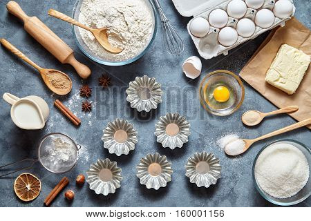The process of making cake dough in Metal bakeware. Baking ingredients for homemade pastry on dark background. Bake sweet cake dessert concept. Top view, flat lay