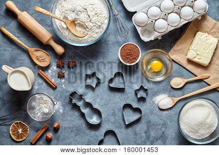 The process of making gingerbread cookies. Baking ingredients for homemade pastry on dark background. Bake sweet cake dessert concept. Top view, flat lay