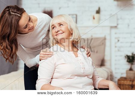 Warm relations. Pleasant smiling young woman taking care of her positive grandmther who is istting in the wheelchair