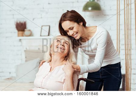 Share your positive emotions. Pleasant delighted elderly woman sitting in the wheelchair and her granddaughter taking care of her while restign at home