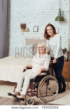 Start a new day with positivity. Pleasant delighted elderly woman sitting in the wheelchair and her granddaughter standing nearby while expressing gladness