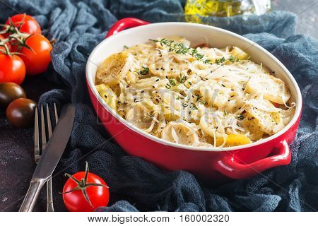 Potato gratin, in rustic dish. Delicious sliced potatoes with onions, tomato, garlic, herbs and chicken meat.