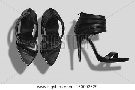 High heeled black sandals shot from the top and from the side isolated on white with strong shadows