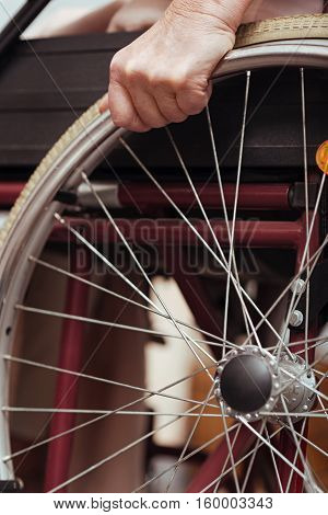 I need it. Close up of wheel of the wheel chair with pleasant elderly woman using it