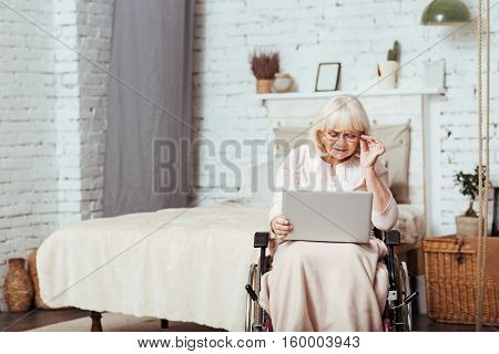 Modern user. Pleasant concentrated elderly woman using laptop and resting at home while sitting in the wheelchair