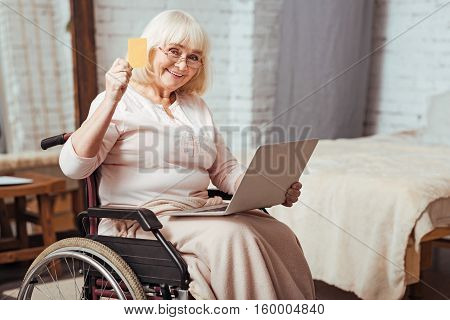 Online service. Cheerful elderly disabled woman holding credit card and using laptop while sitting in the wheelchair