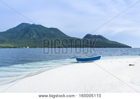 traditional banka outrigger canoe on white beach camiguin island mindanao in the philippines with volcano in the background