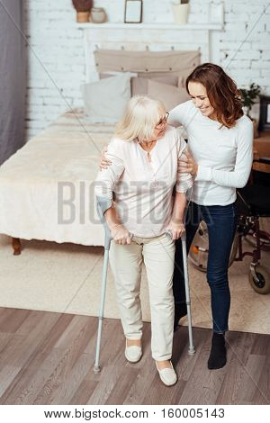 Step forward. Pleasant disabled woman walking with crutches at home while her caring granddaughter helping her