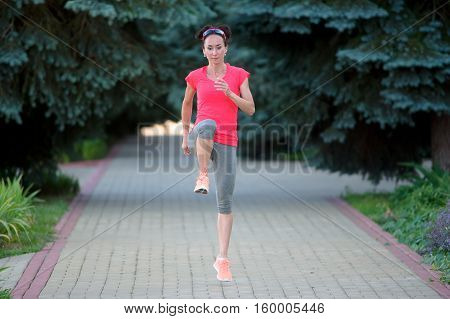 Sportive woman stretching before running. Sportive girl exercising outdoors.