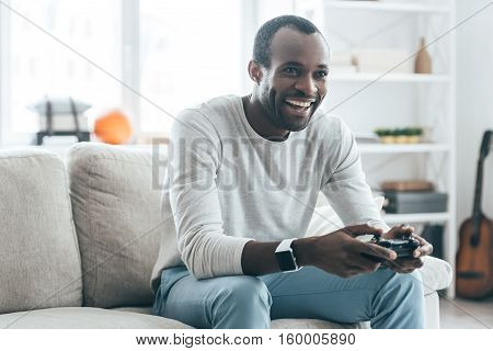 Resting at home. Handsome young African man playing video games and laughing while sitting on the sofa at home