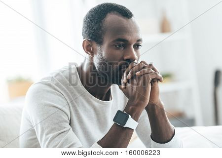 Something on his mind. Handsome young African man holding hands together and thinking while sitting on the sofa at home