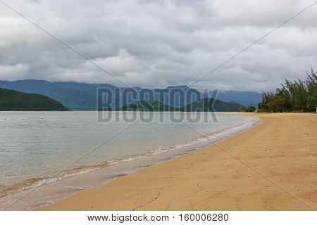 sandy Golden beach with clear sea water green hue, a beautiful secluded place, gloomy foggy sky, on the horizon of many hills, mountains, all covered with greenery