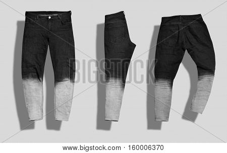 Pair of straight men's jeans with black to white gradient color shot from the front and the back and folded in half isolated on white.